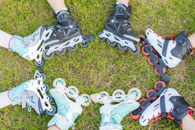 Foto recortada de pessoas com patins inline juntas na grama de um parque