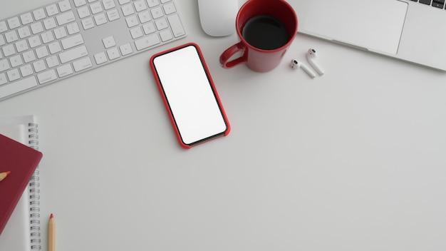 Foto recortada de sala de escritório com telefone de tela em branco e material de escritório na mesa branca