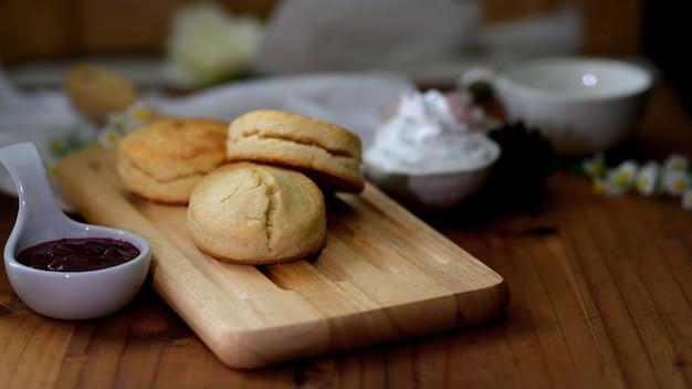 Foto recortada de scones na bandeja de madeira com geléia de morango e creme de leite