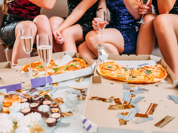 Foto recortada de senhoras sentadas em frente a pizza em caixas, prato com doces e copos com vinho espumante.