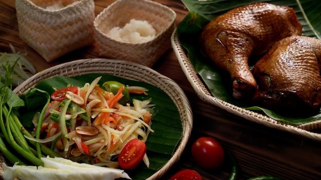 Foto recortada de somtum, comida tradicional tailandesa com frango grelhado e arroz na mesa de madeira