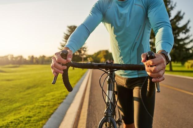 Foto recortada de um atleta ciclista em roupas esportivas caminhando com sua bicicleta após o treino em
