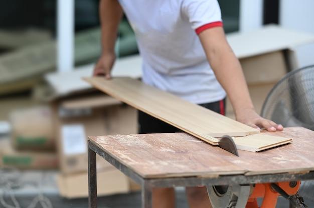 Foto recortada de um carpinteiro cortando um pedaço de madeira em sua oficina de marcenaria.