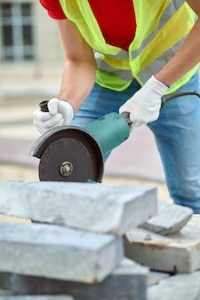 Foto recortada de um construtor experiente cortando um pedaço de ladrilho de concreto usando uma serra circular elétrica