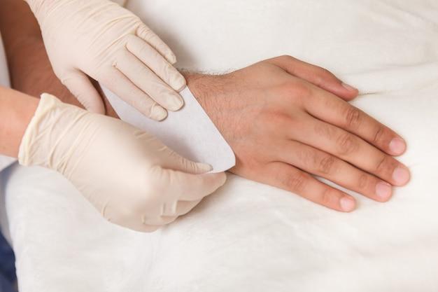 Foto recortada de um cosmetologista fazendo depilação com cera no braço de um cliente do sexo masculino