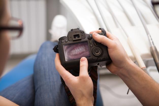 Foto recortada de um dentista mostrando fotos de dentes ao paciente