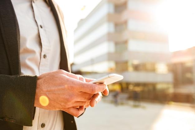 Foto recortada de um empresário europeu em um terno formal, segurando e digitando no celular perto do centro de carreiras