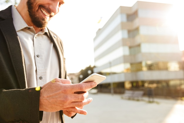 Foto recortada de um empresário ou homem de negócios europeu em um terno formal, segurando e enviando mensagens de texto no celular perto do centro de carreiras