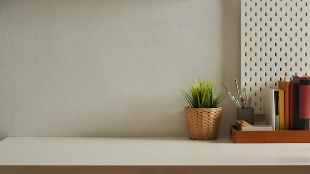 Foto recortada de um espaço de trabalho com livros, artigos de papelaria, vaso de plantas e espaço de cópia no escritório doméstico