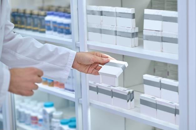 Foto recortada de um farmacêutico com uma túnica branca segurando uma caixa de papelão com medicamentos em uma das mãos