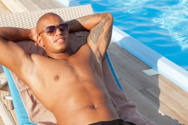Foto recortada de um homem africano bonito usando óculos escuros, deitado ao sol à beira da piscina. homem atraente, bronzeamento perto da piscina