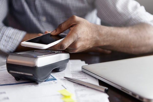 Foto recortada de um homem afro-americano pagando uma conta em um café, usando a tecnologia nfc no celular