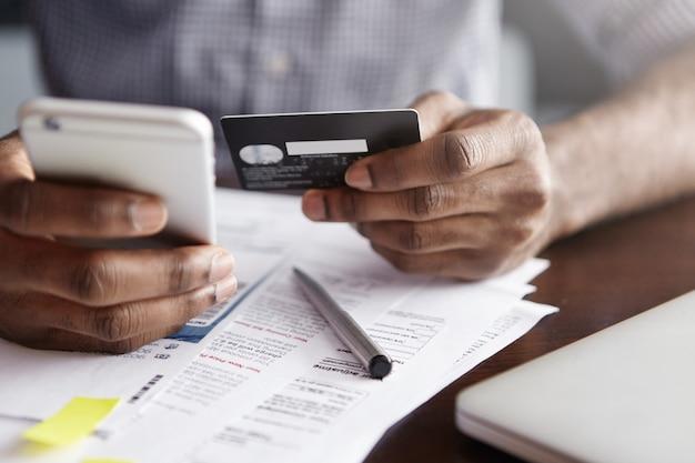 Foto recortada de um homem afro-americano segurando um celular em uma das mãos e um cartão de crédito na outra