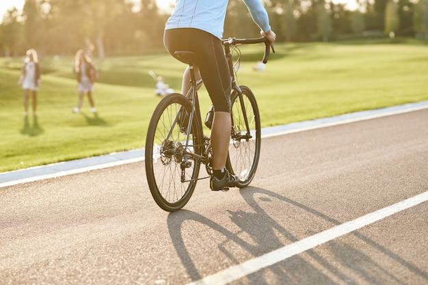 Foto recortada de um homem andando de bicicleta de montanha no parque durante o pôr do sol, pedalando ao ar livre em