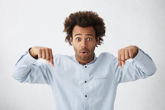 Foto recortada de um homem chocado com cabelo crespo e espesso e olhos escuros usando uma camisa formal apontando para baixo
