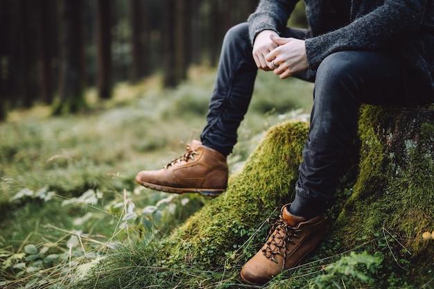 Foto recortada de um homem com barba sentado e pensando na floresta