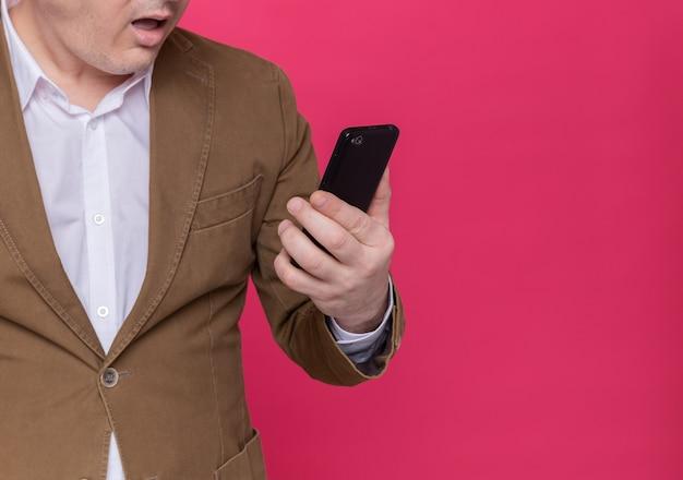 Foto recortada de um homem de meia-idade de terno segurando um celular e olhando para ele espantado