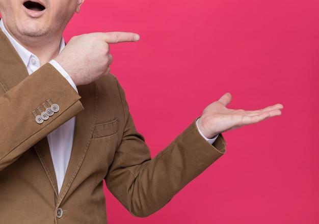 Foto recortada de um homem de meia-idade feliz e surpreso em um terno apontando com o dedo indicador para o lado