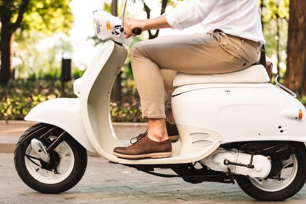 Foto recortada de um homem de negócios jovem bonito caminhando ao ar livre na scooter.