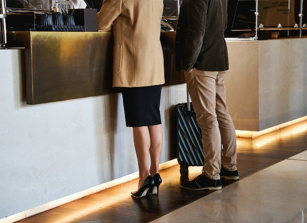 Foto recortada de um homem e uma mulher com suas bagagens durante o check-in no hotel