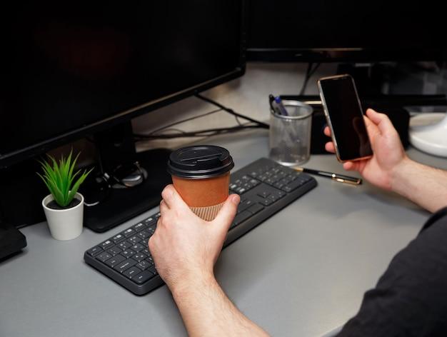 Foto recortada de um homem irreconhecível sentado na cadeira em casa, usando um laptop, navegando na web, bebendo uma bebida quente. trabalhar em casa durante o período de auto-isolamento. negócios, trabalho remoto