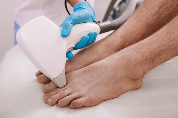 Foto recortada de um homem recebendo procedimento de depilação a laser nos dedos dos pés