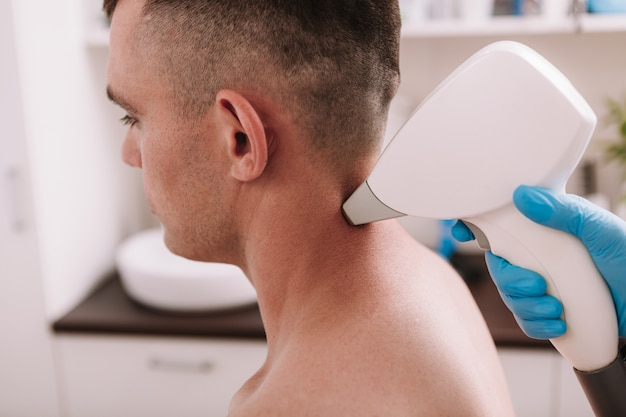 Foto recortada de um homem recebendo tratamento de depilação a laser na clínica de beleza