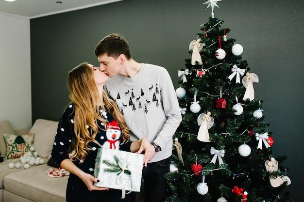 Foto recortada de um homem surpreendendo a namorada com um presente de natal perto da árvore. família dá caixa de presente, night xmas. feliz natal e boas festas! família trocando presentes.