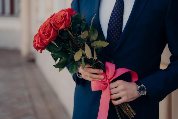 Foto recortada de um homem vestido com um terno clássico, usando gravata azul com camisa branca, com um relógio caro no pulso, segurando um buquê de rosas vermelhas com uma fita enquanto fica sozinho ao lado do prédio