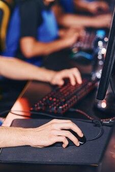 Foto recortada de um jogador de esportes cibernéticos jogando videogame on-line, participando de um torneio de esport, com foco na mão masculina
