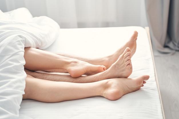 Foto recortada de um jovem casal com os pés descalços saindo de baixo do edredom