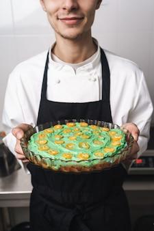 Foto recortada de um jovem e bonito cozinheiro chefe na cozinha cozinhando dentro de casa, segurando o bolo.