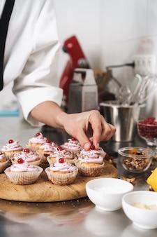 Foto recortada de um jovem e bonito cozinheiro chefe na cozinha cozinhando doces dentro de casa.