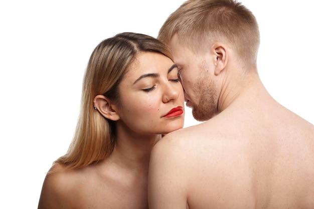 Foto recortada de um lindo casal nu: mulher com nariz redondo e lábios vermelhos fechando os olhos enquanto inala o odor corporal de seu parceiro com a barba por fazer
