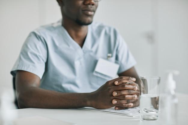 Foto recortada de um médico afro-americano irreconhecível sentado à mesa no escritório de uma clínica médica, copie o espaço