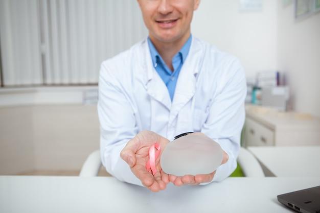 Foto recortada de um médico amigável sorrindo, segurando um implante mamário de silicone e uma fita rosa com o símbolo de conscientização do câncer de mama