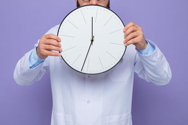 Foto recortada de um médico de jaleco branco segurando um relógio em pé sobre um fundo roxo