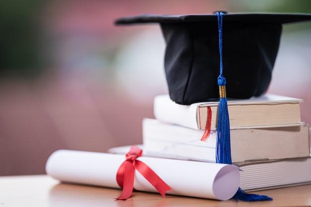 Foto recortada de um mortarboard de chapéu de formatura de universidade e certificado de diploma em cima da mesa