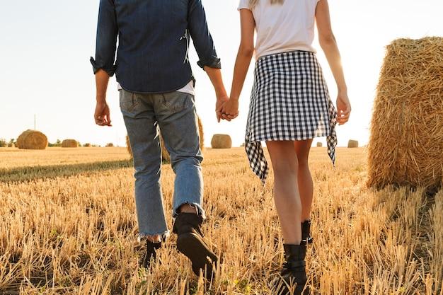 Foto recortada de um rapaz e uma garota caminhando por um campo dourado com um monte de montes de feno, durante um dia ensolarado
