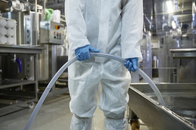 Foto recortada de um trabalhador irreconhecível lavando equipamentos em uma fábrica de produção de alimentos limpos, copie o espaço