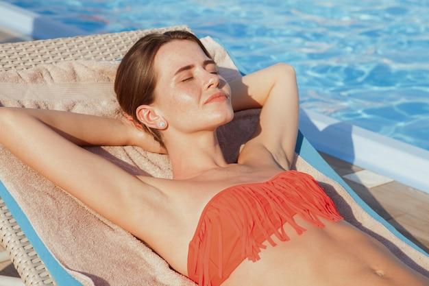 Foto recortada de uma bela jovem de biquíni, desfrutar de banhos de sol perto da piscina. mulher linda bronzeamento à beira da piscina