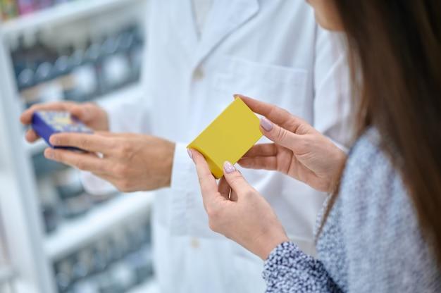Foto recortada de uma cliente de cabelos escuros e um farmacêutico com uma túnica branca segurando barras de sabão nas mãos