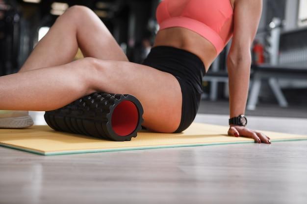 Foto recortada de uma esportista irreconhecível usando rolo de espuma para aliviar dores nos isquiotibiais