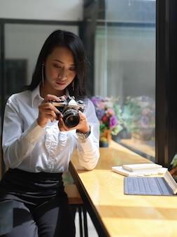 Foto recortada de uma foto grapher feminina verificando a foto na câmera digital enquanto trabalhava no estúdio