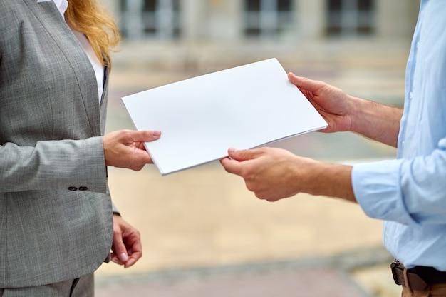 Foto recortada de uma inspetora caucasiana loira elegante entregando a documentação do prédio para seu colega