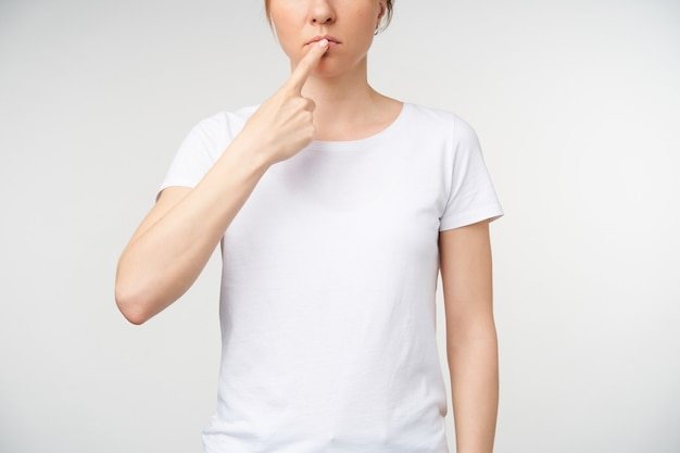 Foto recortada de uma jovem com maquiagem natural, mantendo o dedo indicador sobre os lábios enquanto mostra a língua de trabalho na linguagem de sinais, em pé sobre um fundo branco