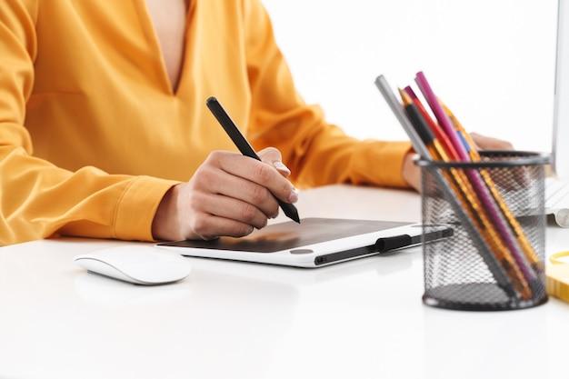Foto recortada de uma jovem designer europeia usando um computador tablet gráfico e uma caneta stylus enquanto trabalhava em um escritório bem iluminado