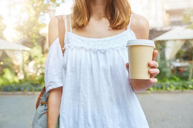 Foto recortada de uma jovem elegante e atraente usando um vestido branco de verão com uma xícara de café para viagem, caminhando ao ar livre no parque