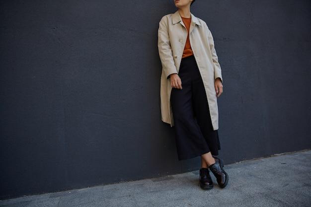 Foto recortada de uma jovem hippie vestida com culotes pretos, suéter sexy e trincheira bege, posando sobre uma parede urbana negra com roupas da moda e sapatos de couro