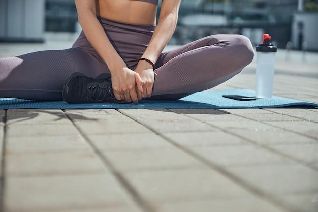 Foto recortada de uma jovem iogue branca esbelta, com roupas esportivas, sentada em um tapete